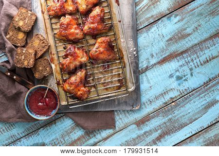 Top view dinner table with homemade chicken wings and cranberry sauce. Rustic style