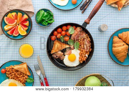 Breakfast table with healthy food. Fried eggs bacon tomatoes beans and spinach in a frying pan on a table with various fruits and croissants top view. Tasty and healthy food