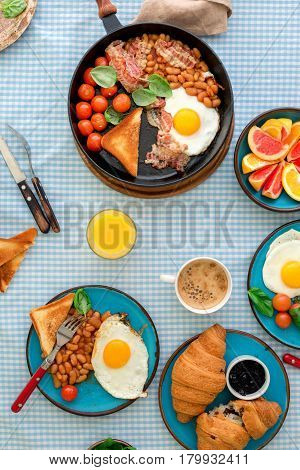 Breakfast table with healthy food. Fried eggs bacon tomatoes beans and spinach in a frying pan on a table with various fruits and croissants top view