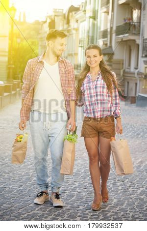 Portrait of man and woman in full lenght carrying bags full of food and drinks for tomorrow picnic. Toned image.