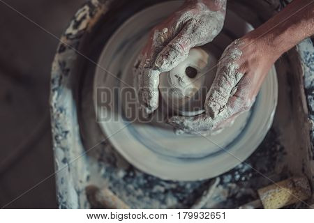 Hands of a potter making pottery