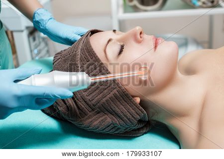 Face Beauty Treatment. Beautician makes Facial Darsonval Therapy for woman using high frequency D'Arsonval