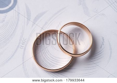 Closeup of Two classical gold wedding rings on a white textured background with copy space. Love and marriage proposal concept.