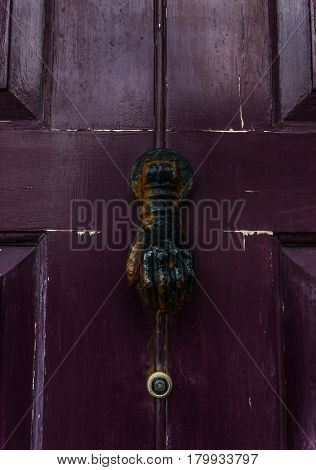 Old Cast Iron Knocker In The Shape Of A Hand On A Purple Door, Rusty Decoration On The Door