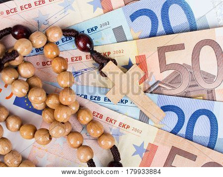 Closeup of a wooden rosary on Euro banknotes