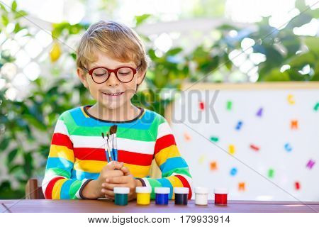 Funny adorable little kid boy with glasses holding watercolors and brushes. Happy child and student is back to school. Education, school, learning concept. School, preschool nursery equipment