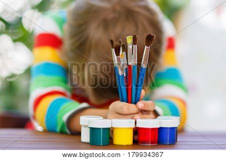 Sad and confused little kid boy holding watercolors and brushes. Unhappy child and student is back to school. Education, school, learning concept. School, preschool nursery equipment