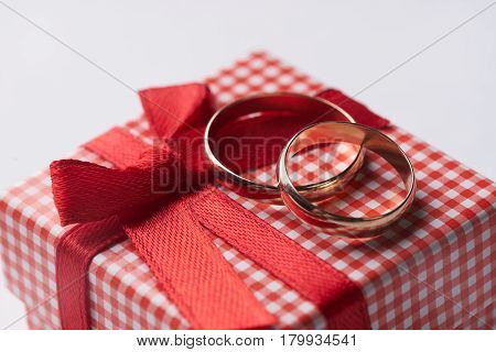 Close-up of two gold Wedding rings and Gift box for wedding with red bow on isolated white background. Love and marriage proposal concept.