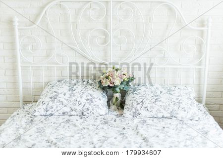 Wedding bouquet with white and pink tulips and pink small roses on a bridal bed with black and white bedclothes on a brick background