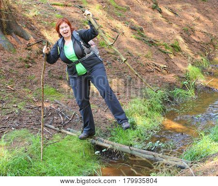 Overweight woman balancing on a footbridge over forest brook. Dangerous situation during summer vacations. Health and insurance theme.