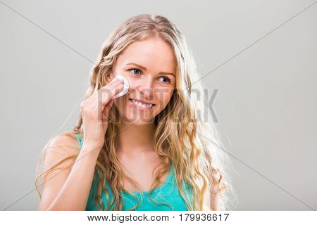 Beautiful young woman cleaning her face with cotton pad on gray background.