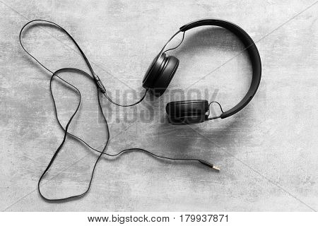 Black headset with cord on a concrete background