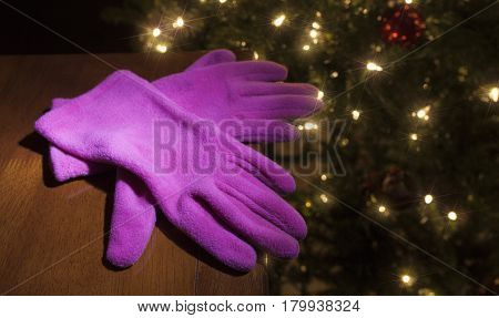 New pink gloves with a Christmas tree lit behind