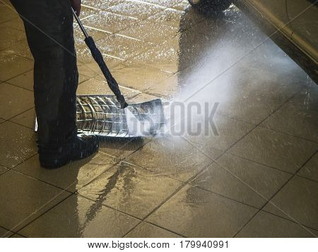 The worker washes water jet car mat