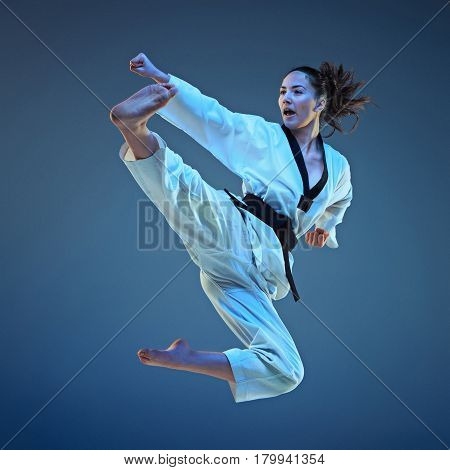 The karate girl with black belt jumping on blue background