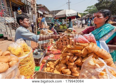 BADAMI, INDIA - FEB 8, 2017: Trader selling crackers sweet pies and bread to indian woman on busy street of Karnataka state on February 8, 2017. Population of Karnataka is 62000000 people