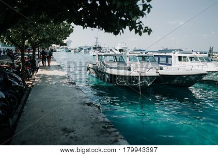 Male, Maldives - December 17, 2016: Motorcycles and boats in the city of Male the capital of the Maldives