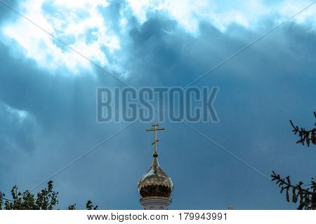 Golden Russian orthodox cross at the orthodox church roof top against blue sky