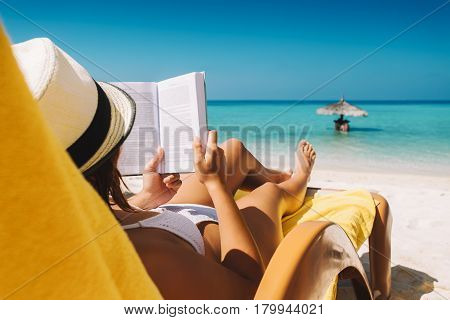 Woman On Sunbed Reading Book At Tropical Island