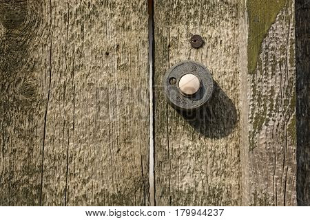Close up of obsolete button doorbell on wooden wall with
