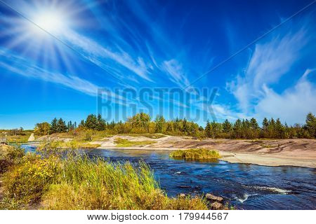 Indian summer in Manitoba, Canada. Improbable plumose clouds and the autumn sun over the river Winnipeg. The concept of ecological and recreational tourism