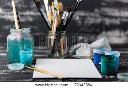 Artist's workshop.Items for children's creativity on a wooden background. Acrylic paint and brushes on white wooden background. Picture with copy space and for add text. some art stuff on wooden table