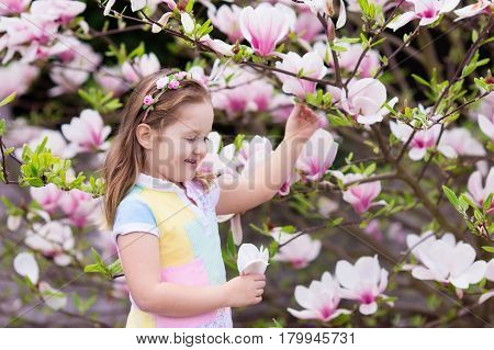 Child With Magnolia Flower. Little Girl With Flowers