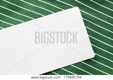 Blank white label on green striped cloth as a background