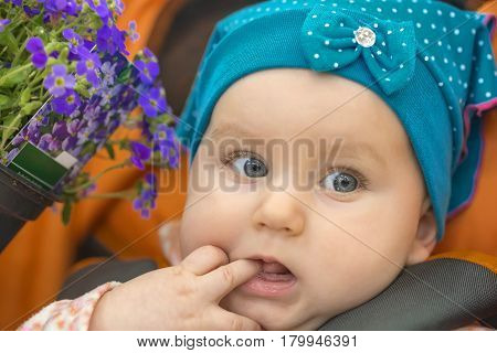little nice girl in a blue kerchief, holds two fingers in a mouth
