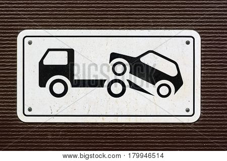 Closeup of sign forbidding parking with tow truck on it on dark background