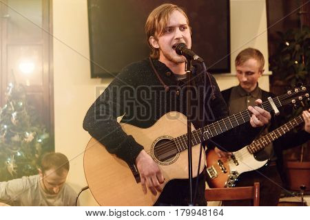 Stylish Vocalist With Beard Performing Lyrical Song On Stage With His Band