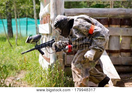 MOSCOW - JUNE 23, 2012: Paintball sport player takes cover in shelter.