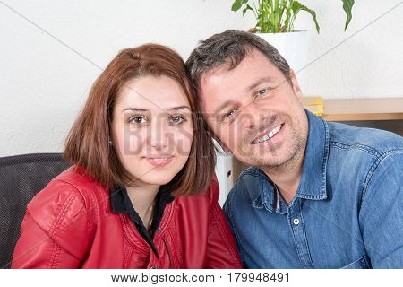 Smiling young business woman flirting with a man in the office making selfie