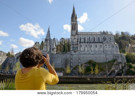 brunette woman photographs the cathedral in Lourdes France