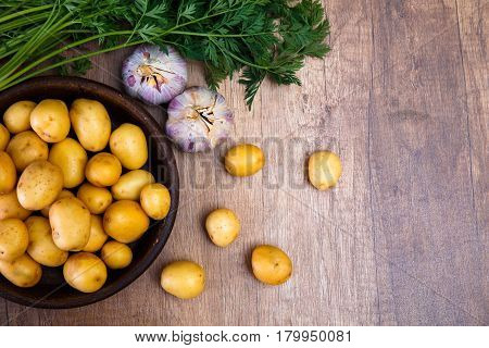 Potatoes in plate. Carrot tops, garlic and raw new potato. Fresh natural vegetables. Organic bio food on rustic wooden table.