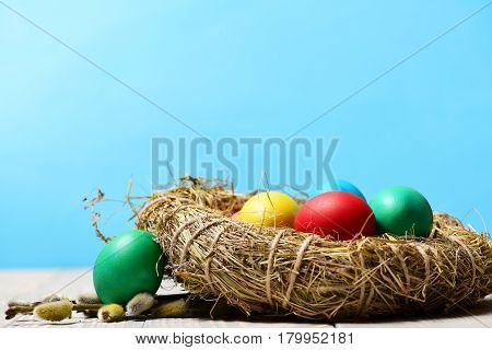 Colorful Painted Eggs In Bird Nest On Wooden Background, Easter