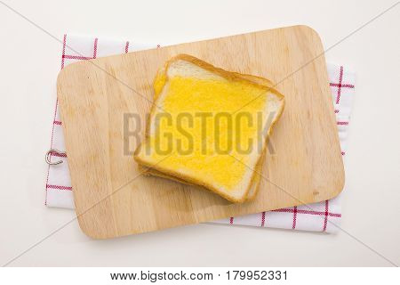 sweet toast butter on wooden chopping board with dish towel decoration on white background. this bread is thai style sweetmeat.
