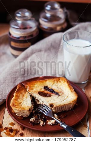 Cottage cheese casserole with figs and raisins with a glass of milk on a wooden background. A cracked cheesecake with figs and milk. Cupcake with figs nuts and raisins on a wooden background.