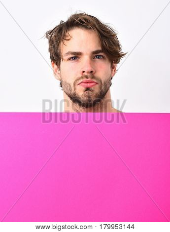 Bearded man short beard. Caucasian sexy young macho with stylish hair and moustache on serious face holding fuchsia or pink paper sheet isolated on white studio background copy space