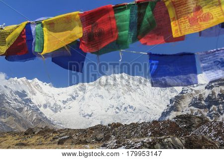 Himalaya Annapurna One mountain peak and prayer flags in blue sky view from Annapurna base camp famous trekking destination in Nepal.