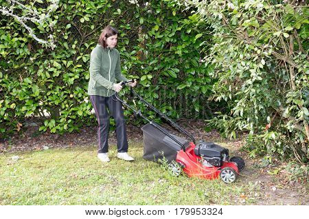 Woman Mows The Lawn Between The Trees In Her Garden