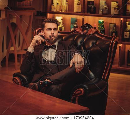 Confident upper class man smoking cigar in gentlemen's club