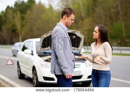 Couple near broken car on a highway roadside
