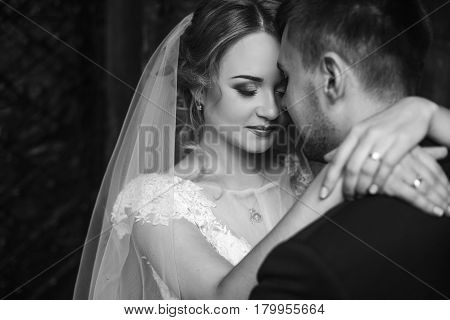 Happy newlywed couple portrait face closeup of newlywed blonde bride hugging smiling groom near old metal gate emotional couple on honeymoon