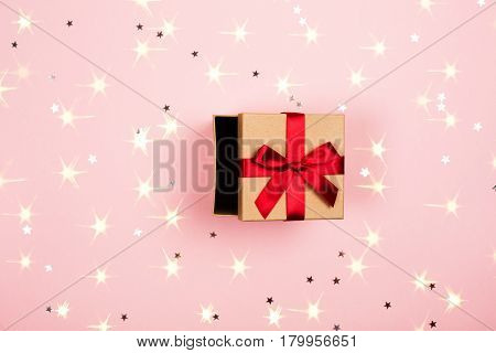 Opened present box with red bow on pink background with tittle sparkles. Flat lay style.