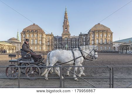 COPENHAGEN DENMARK - DECEMBER 24 2016: Horses and cart with rider at Christianborg palace courtyard in Copenhagen Denmark