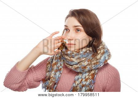 Young girl wrapped in scarf using medicament for nose isolated on white background.