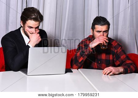bearded men businessmen long beard brutal caucasian hipster with moustache hold glass with whiskey has serious face unshaven guys with stylish hair in suit and red tie with laptop