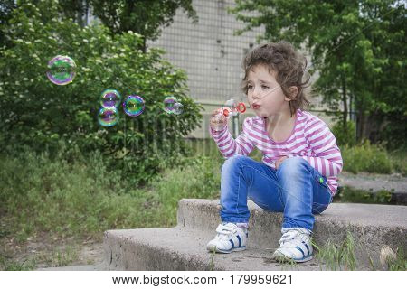 Summer in the park sitting on the steps of small curly girl and blowing soap bubbles.