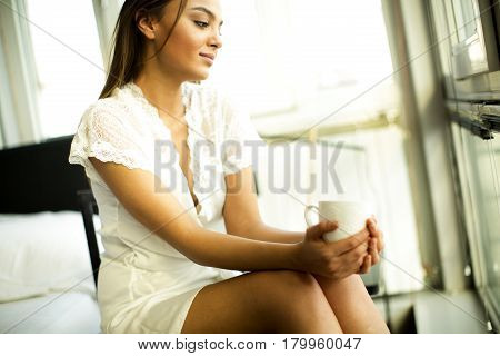 Young Woman Drinking Coffee And Dreaming On A Chair By The Window In Her Nightgown